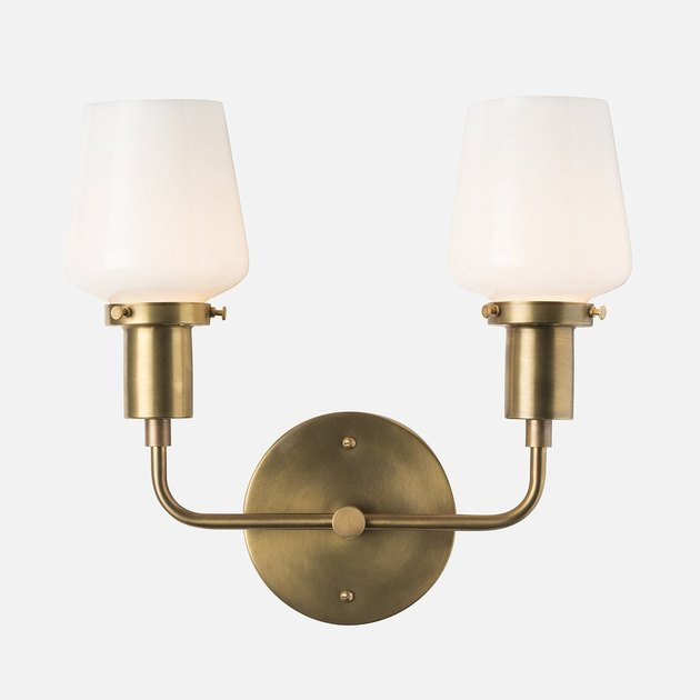 Brass wall sconce with two L-shaped lights featuring white shades