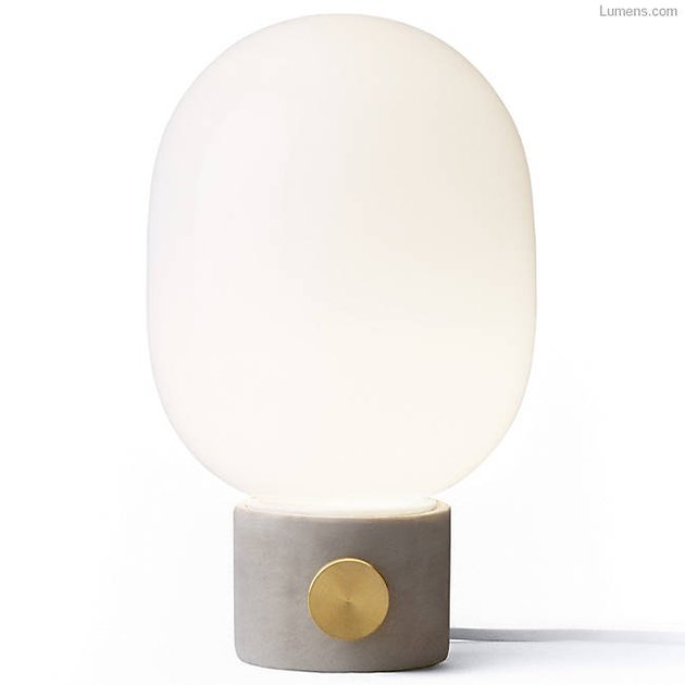 Oval white globe table lamp with concrete base and brass circular knob