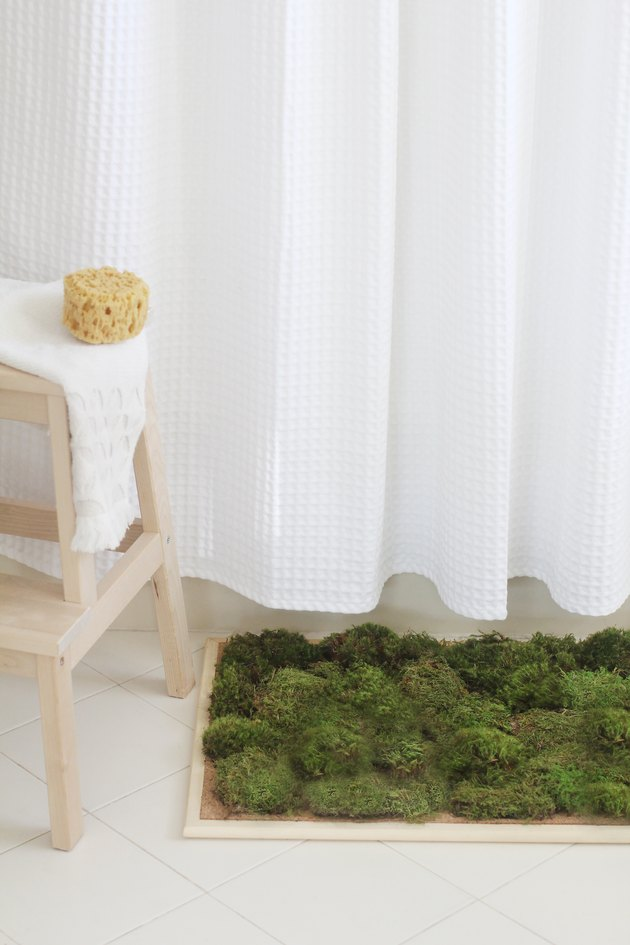 Moss shower mat in front of tub