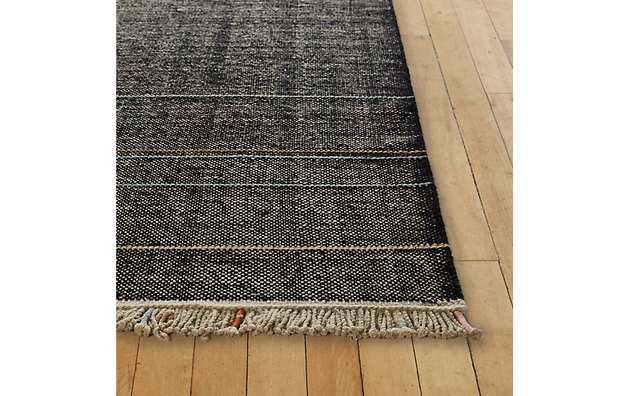 Black rug with white specks and cream fringe