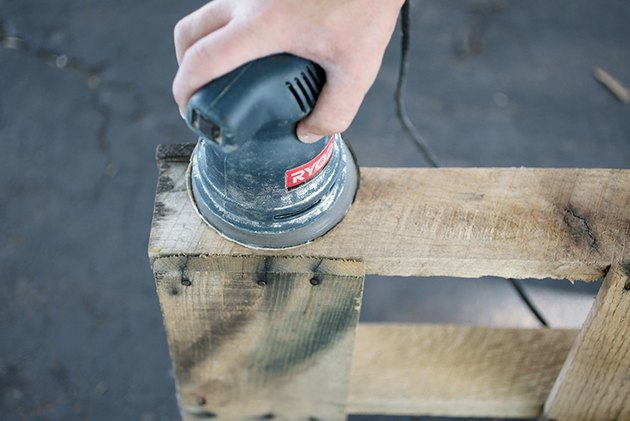 Orbital sander sanding piece of wood.