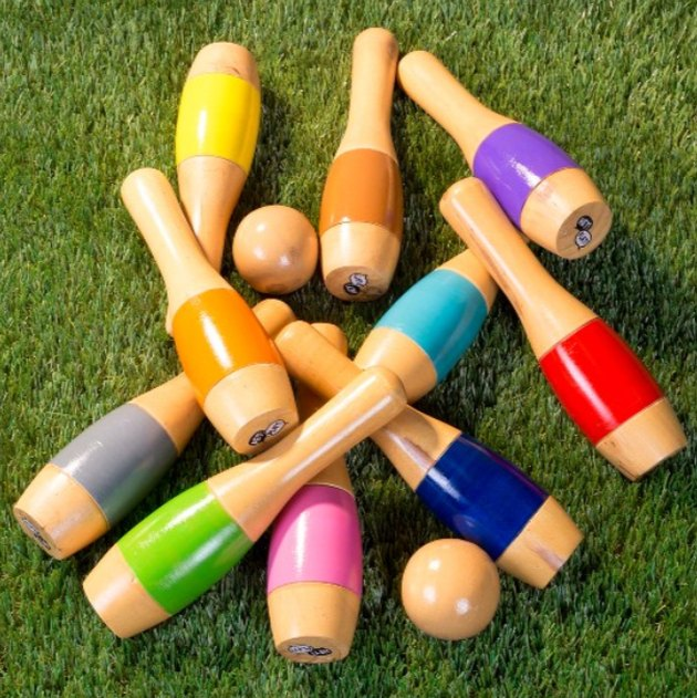 Colorful wooden bowling pins lay on a grass lawn.