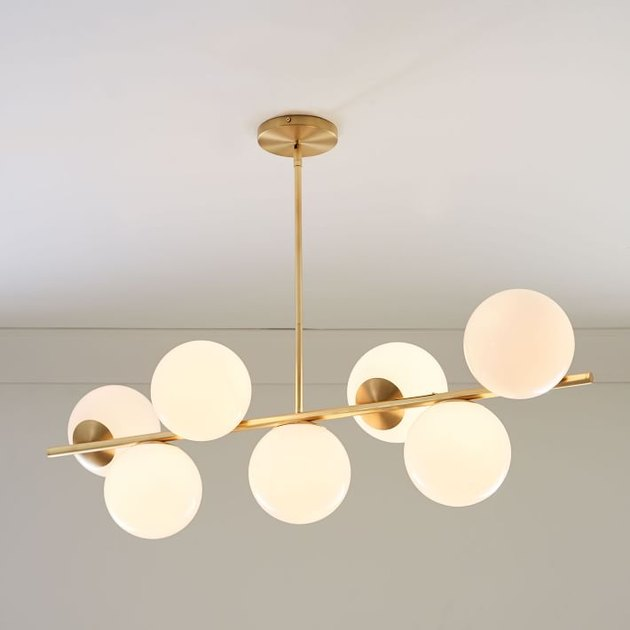 Brass modern light fixture with seven round bulbs in varying positions
