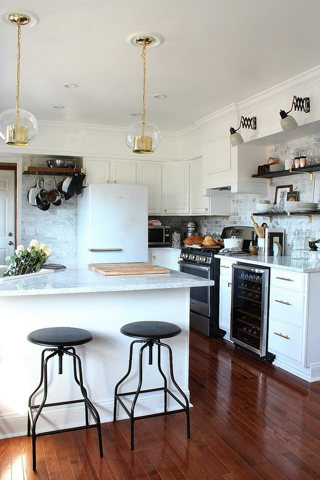 An open kitchen with marble tile and white cabinets and task and pendant lighting.