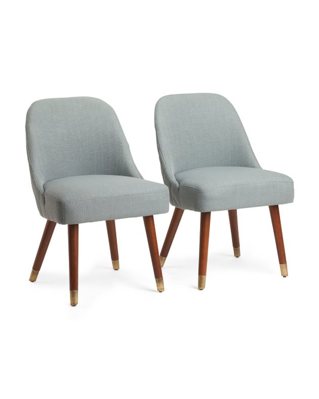 Two wood-legged dining chairs with plain linen upholstery.