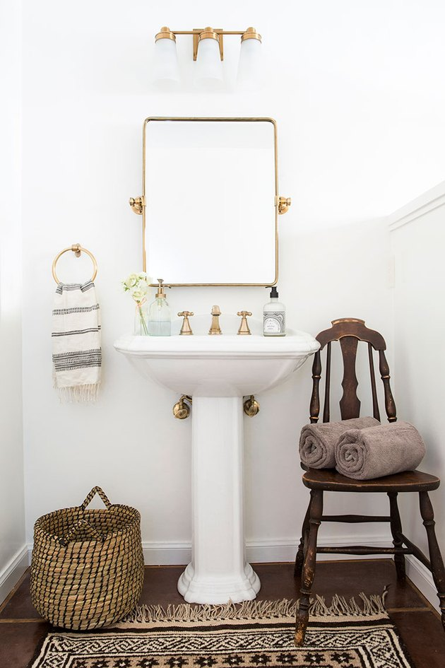 White bathroom pedestal sink with brass accents and area rug on wood floor