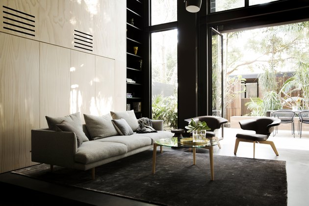 Living room with gray couch, gray chairs, plywood wall, and big windows.