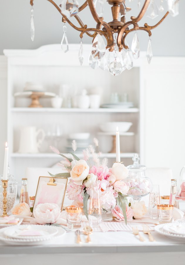 A white table with pale pink flowers and rose god metallic accents.
