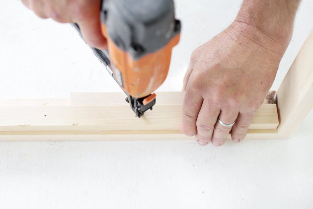nailing a piece of wood to wooden frame.
