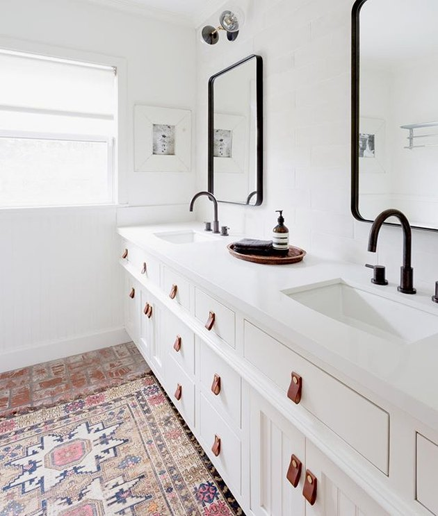 White bathroom with black faucets and tan leather drawer pulls