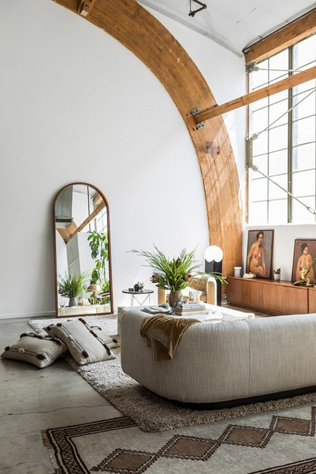 Living room with arched beams and mirror and curved gray couch