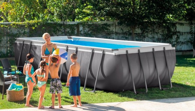 Family playing near above-ground swimming pool