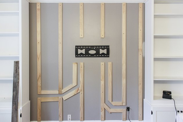 Boards attached to wall with wood paths for wires