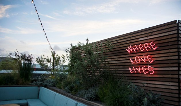 "Rooftop bar with ""Where Love Lives"" neon sign."