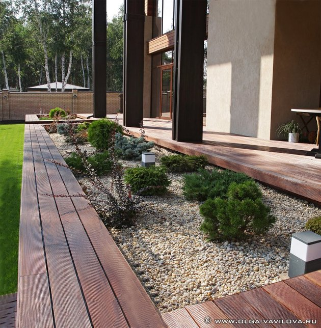 wooden deck with rectangular cutout shrub and rock garden