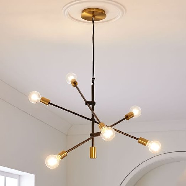 Modern chandelier with geometric lines, bare bulbs, and gold bases.