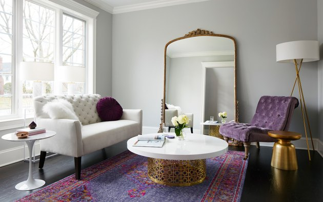 Tufted velvet purple chair in room with white color palette and brass accents