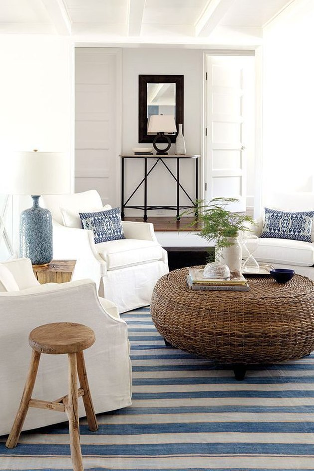 White armchairs circled around roud woven coffee table