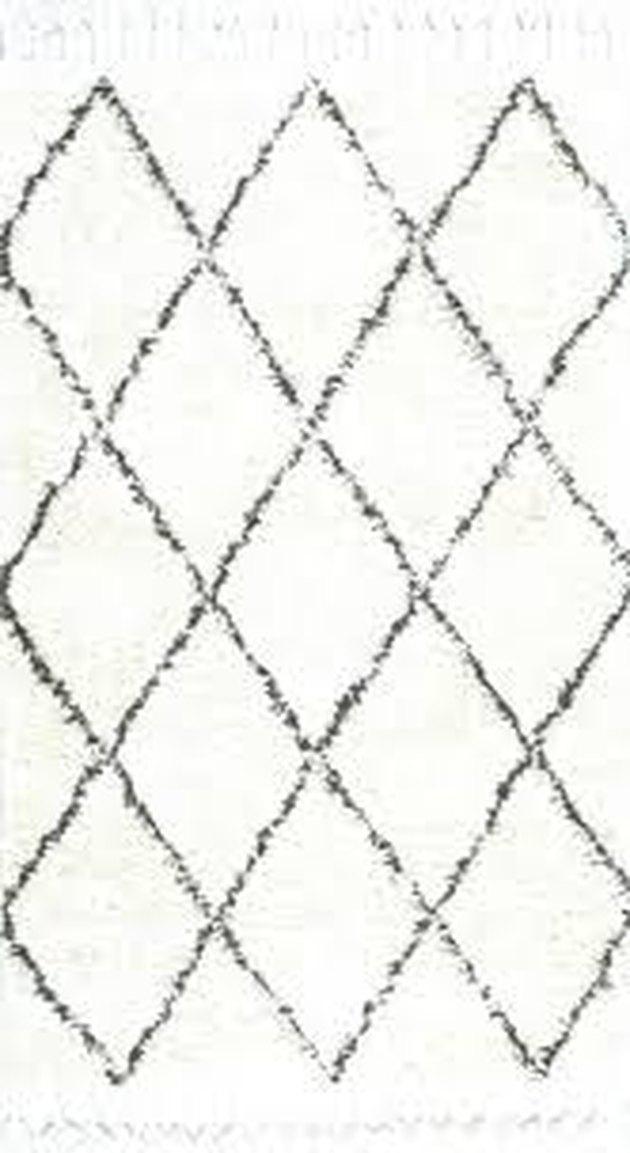 Black and white diamond area rug with fringe