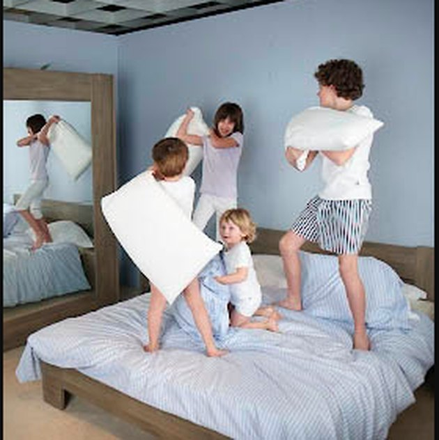 Kids playing on a bed.