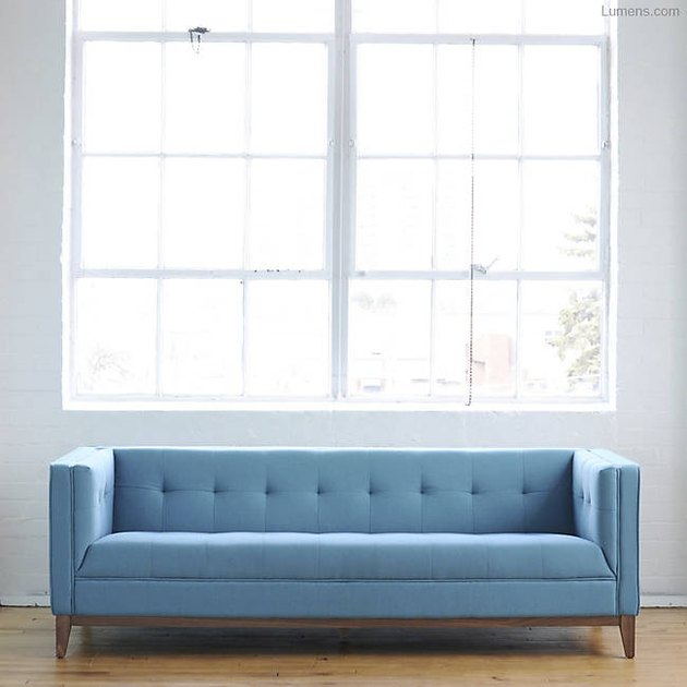 A blue sofa beneath a large sunny window.