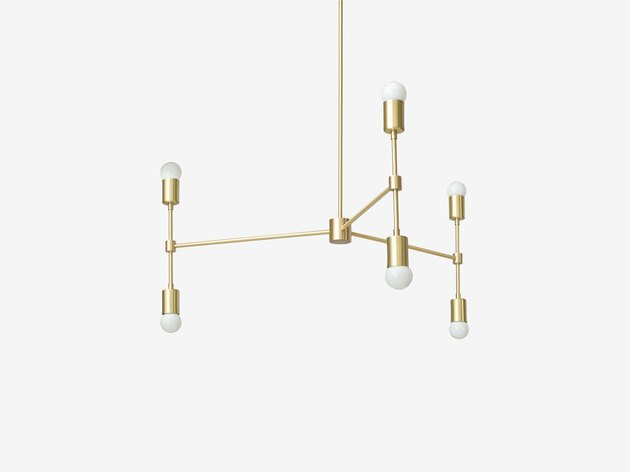 Brass pendant light with three vertical prongs featuring light bulbs on top and bottom of each