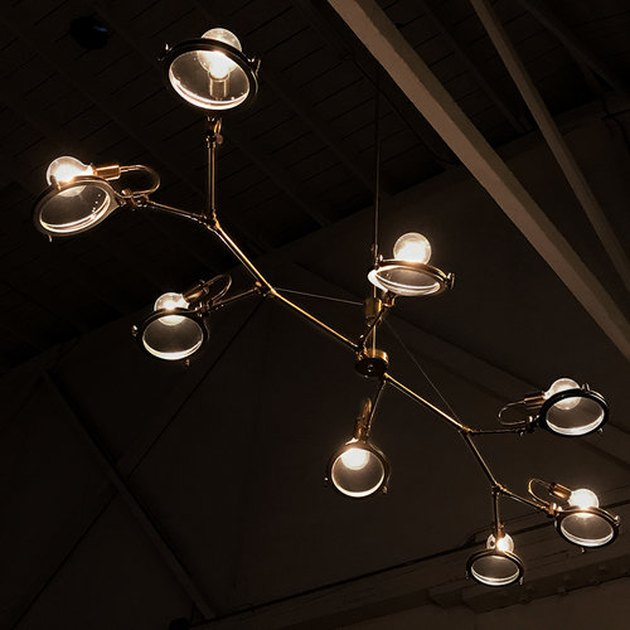 Modern chandelier with eight bare bulbs behind magnifying lenses