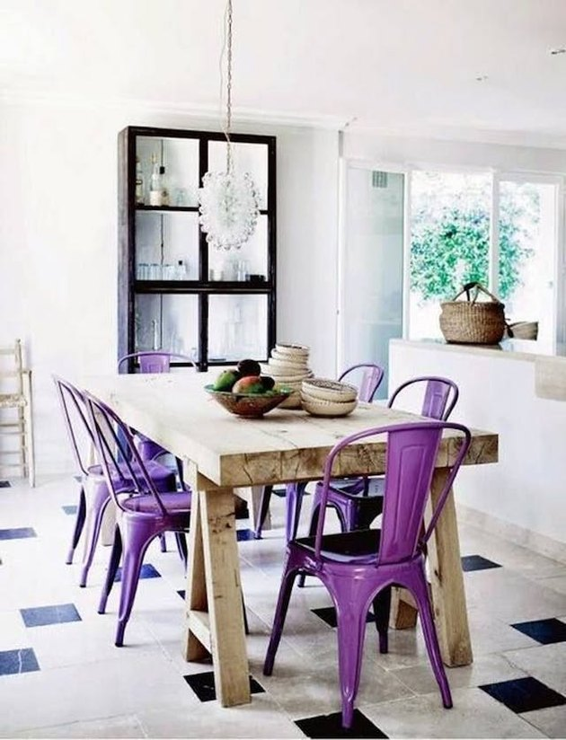 Raw wood kitchen table surrounded by bright purple metal dining chairs