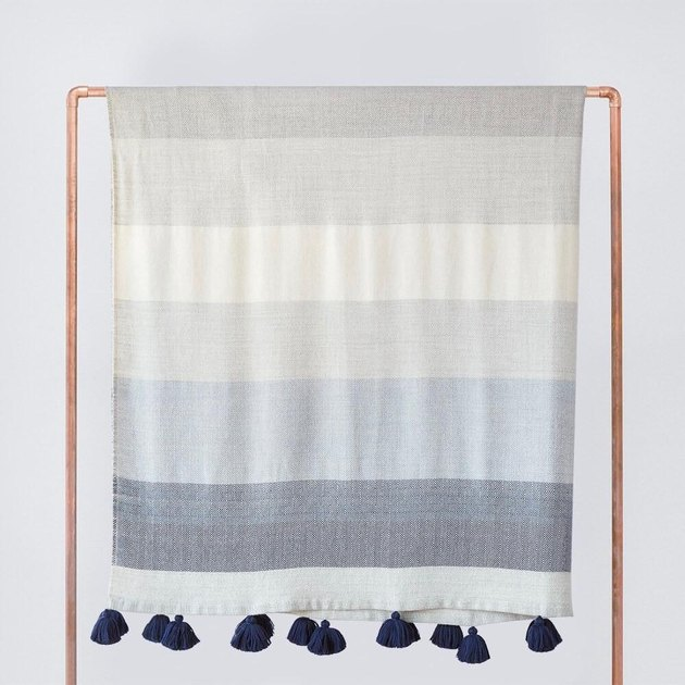 Pale blue, light gray and white striped throw blanket with navy tassels