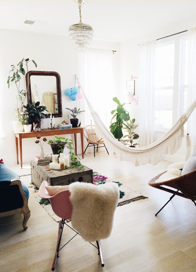 A hammock stretches across a wide window in a living room