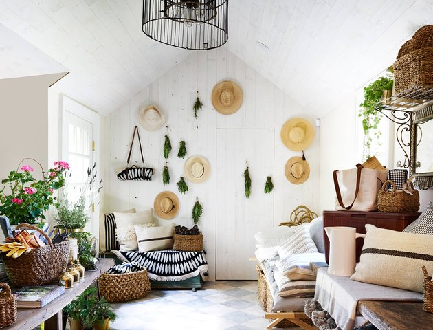 Hats and greenery hang on a white wall in an eclectic room