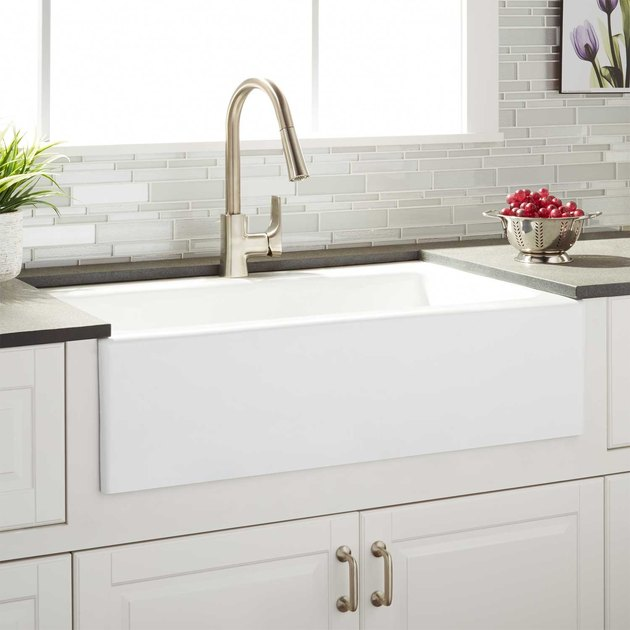 White farmhouse sink with silver arched faucet