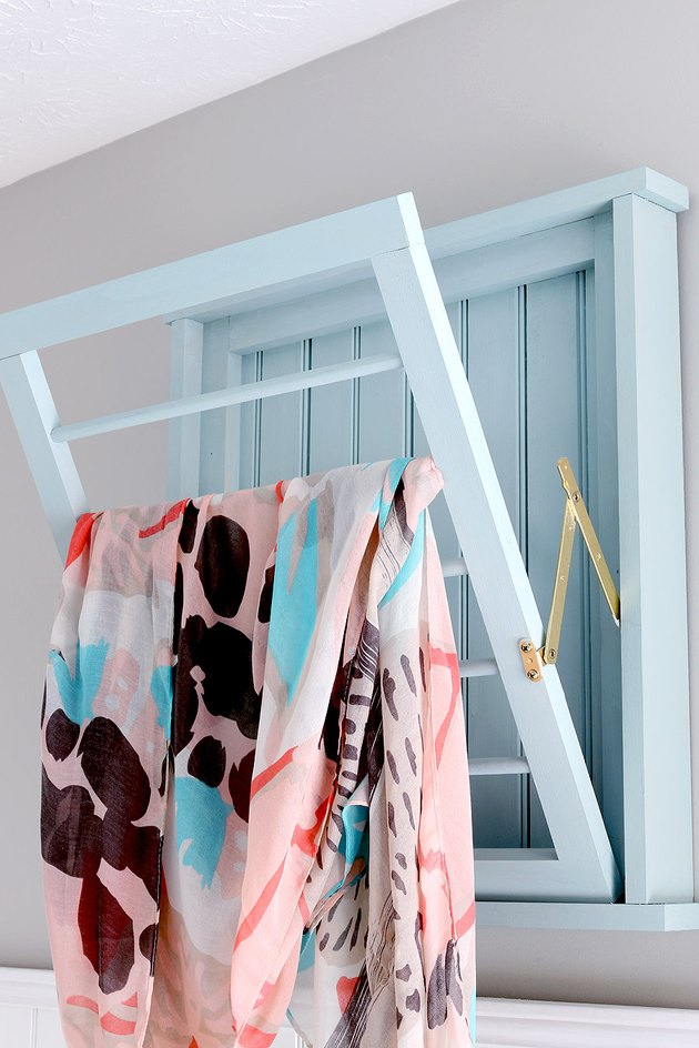 A light blue drying rack with a gold hinge.