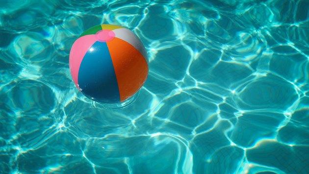 Beachball floating in swimming pool.