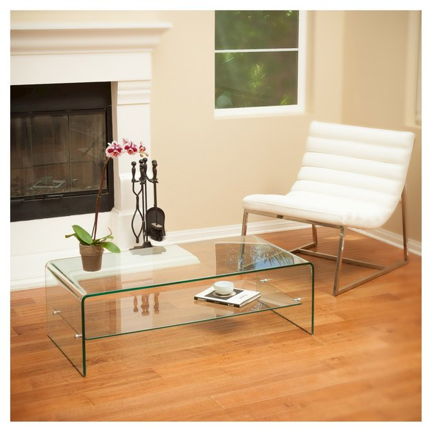 Minimal room with natural wood floors featuring an all-glass coffee table in rectangular shape.