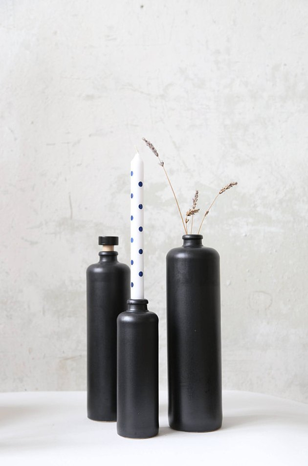Three matte black cylinder bud vases in varying heights