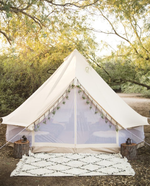 A photo of a white tent with mesh sides and tassels in the woods
