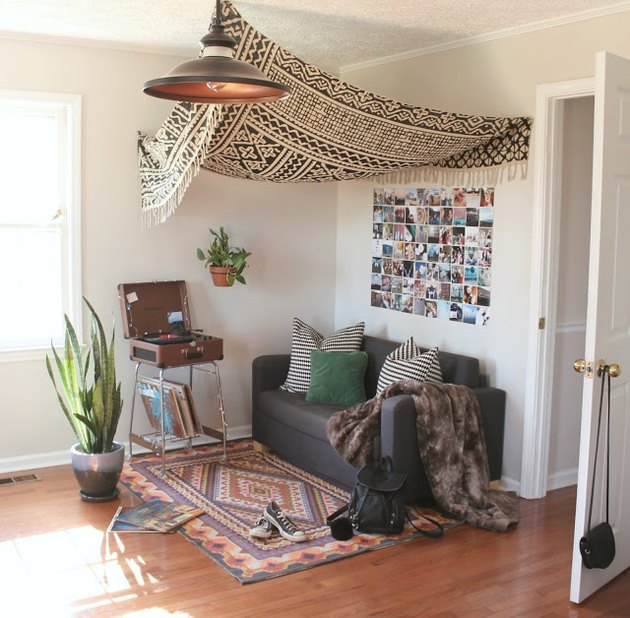 A black-and-white tapestry hangs over a gray couch and patterned rug