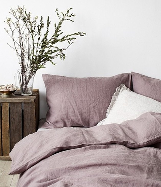 Ash-rose linen bed sheet next to a wooden night stand,