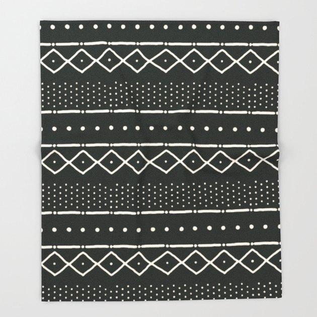 Black throw blanket with white geometric stripes