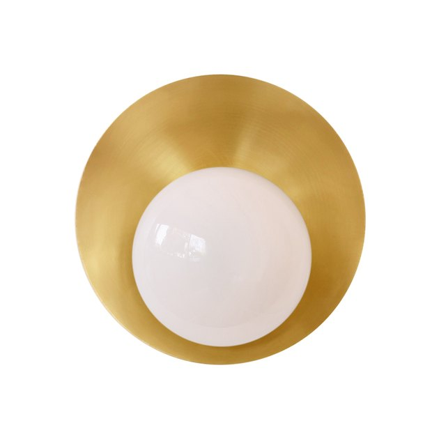 Wall sconce with single bulb on circular brass base