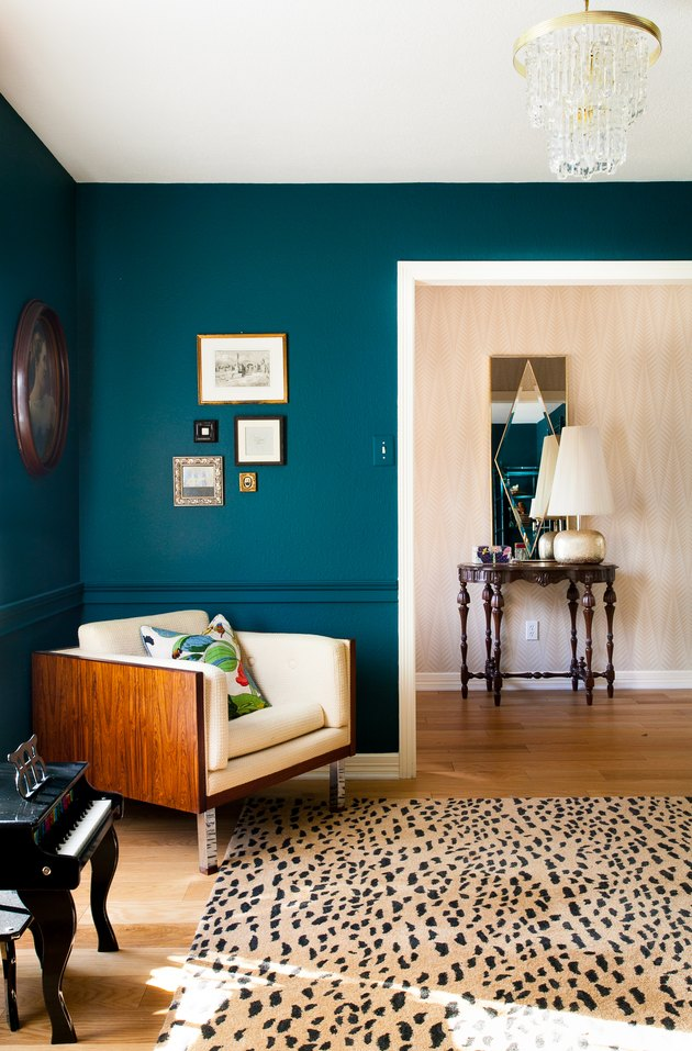 dark greenish blue paint color in sitting room with armchair and patterned rug