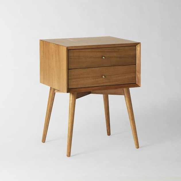 Minimal wooden mid-century nightstand with long legs and medium finish