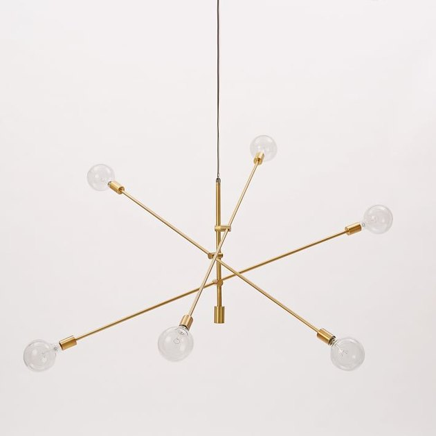 Modern chandelier featuring brass geometric lines and round bulbs