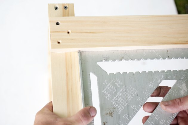 two pieces of wood with square tool.