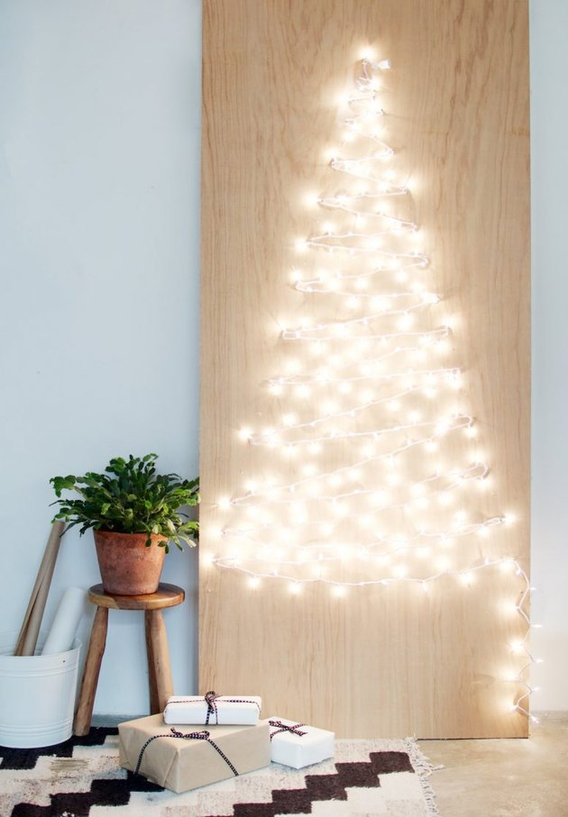 Christmas tree made from small string lights on plywood panel