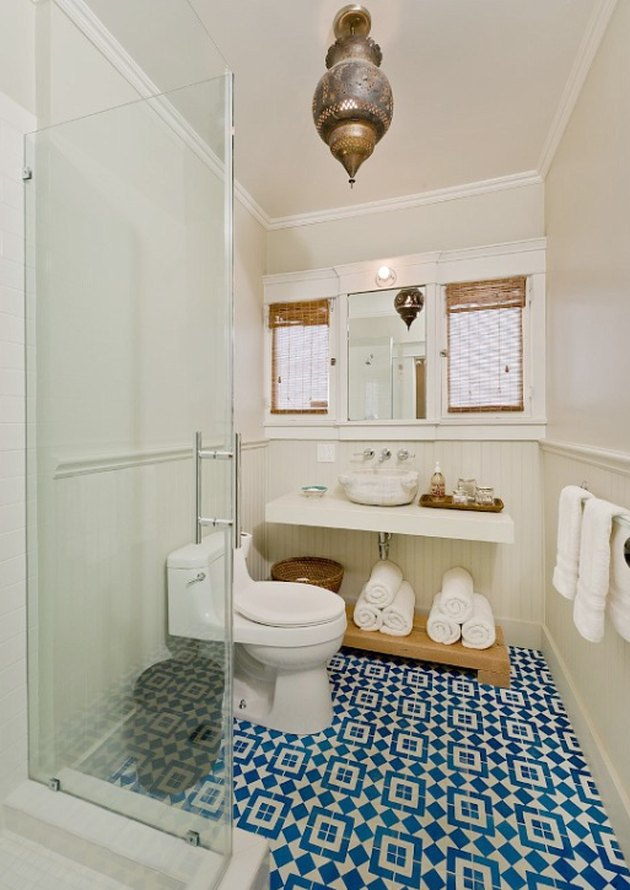 Photo of bathroom with glass walk-in shower and blue-tiled floor.