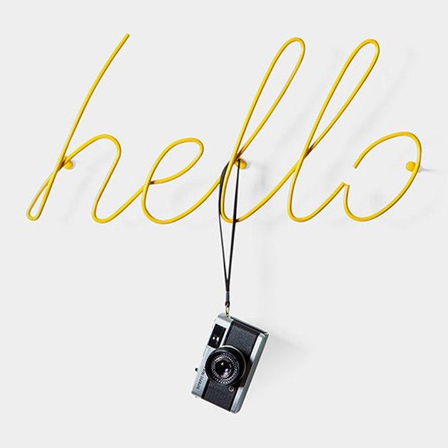 """MoMA metal coat rack bent in shape of the word """"hello""""."""