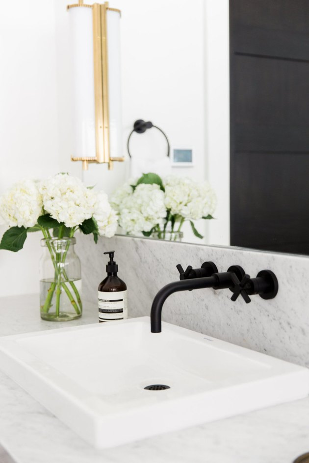 black wall-mount faucet with cross handles