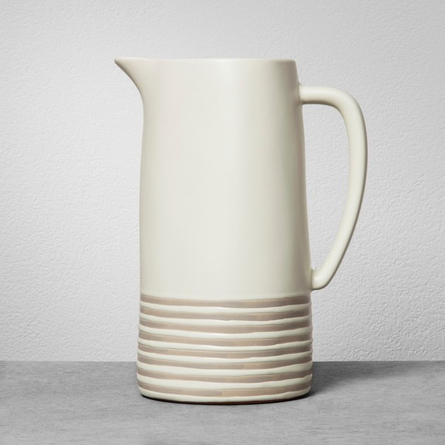Cream ceramic pitcher with thin beige stripes on the lower third
